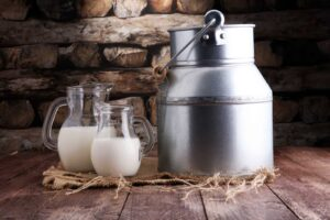 A jug and glasses of pasteurized milk sitting on a wooden table